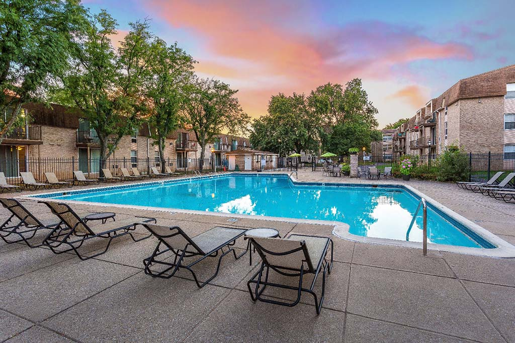 An outdoor pool with lounge chairs and umbrellas with a beautiful sunset at 450 Green apartments for rent