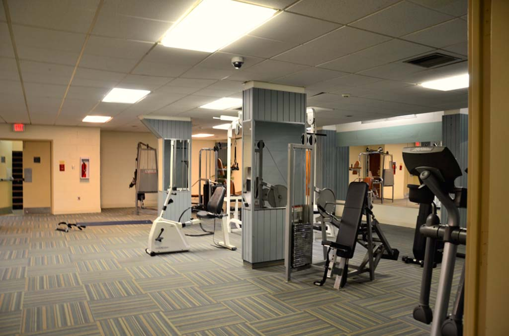 A gym with exercise equipment at Academia Suites apartments for rent