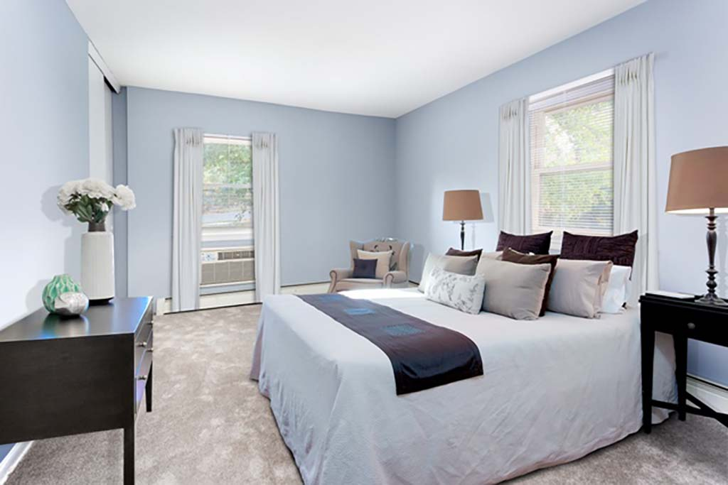 A bedroom with a bed and open windows at Bromley House apartments for rent