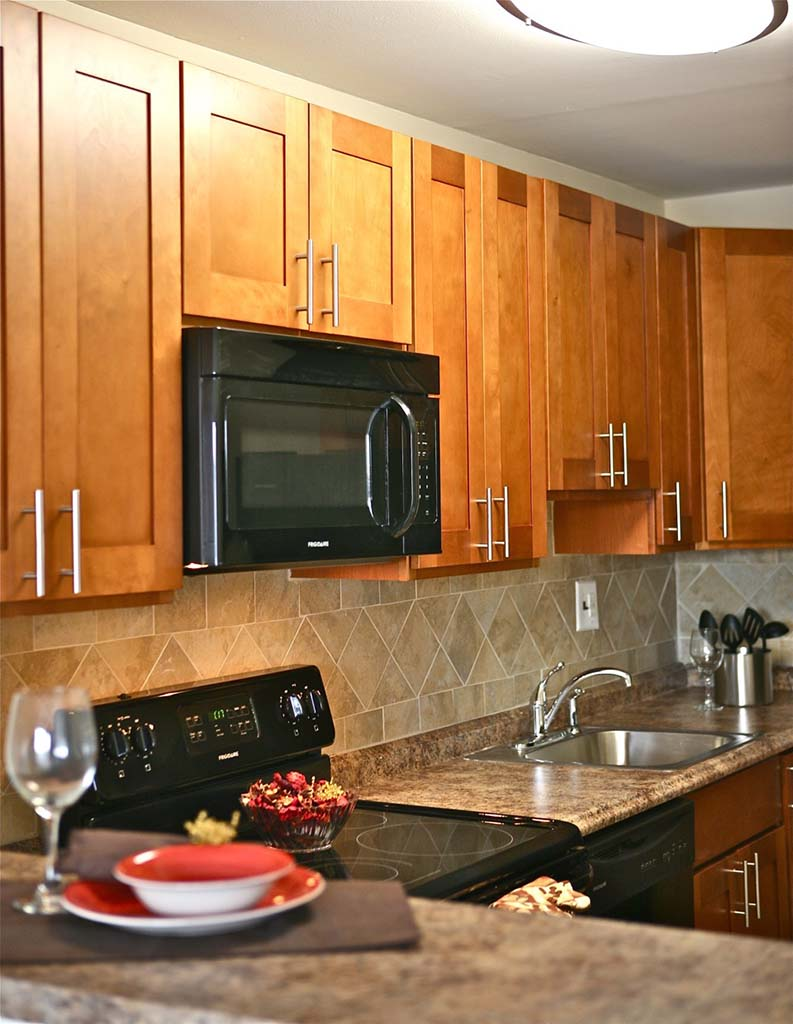 Kitchen with an oven, sink, and wine glass at Chelboune Plaza apartments for rent