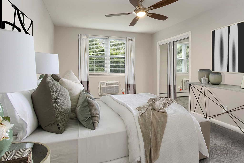 Bed with a ceiling fan and an open window at Gardens of Mt. Airy apartments for rent