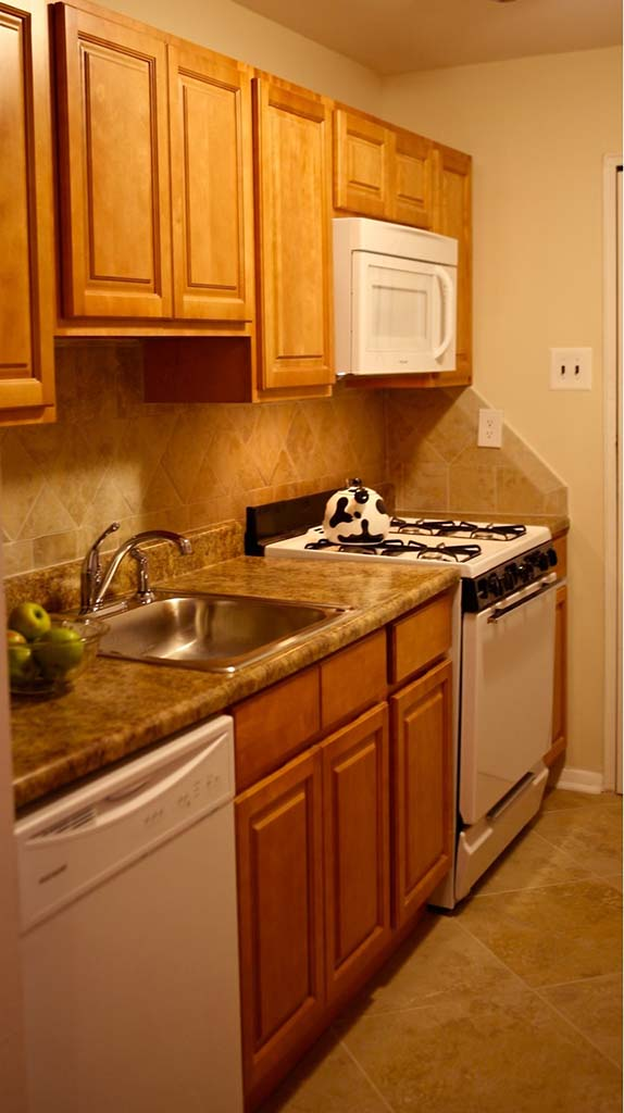 Kitchen with brown cabinetry at Joshua House apartments for rent in Philadelphia, PA