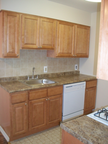 Kitchen with brown cabinetry at Longwood Manor apartments for rent