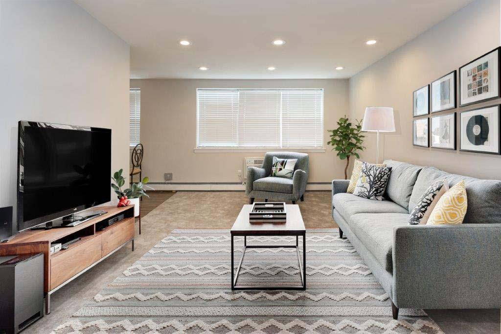 Living room with a couch, chair, and TV at Mt Airy Place apartments for rent in Philadelphia, PA