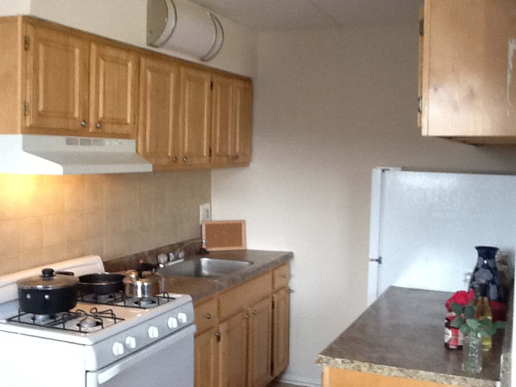 Kitchen with white appliances and brown cabinetry at Olney Plaza apartments for rent in Philadelphia, PA