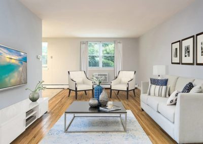 Living room with a couch, two chairs, and a TV at Olney Plaza apartments for rent in Philadelphia, PA