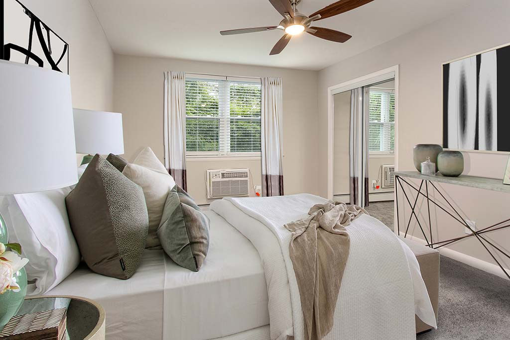 Fully furnished bedroom with a ceiling fan and open window at Rosedale Court apartments for rent