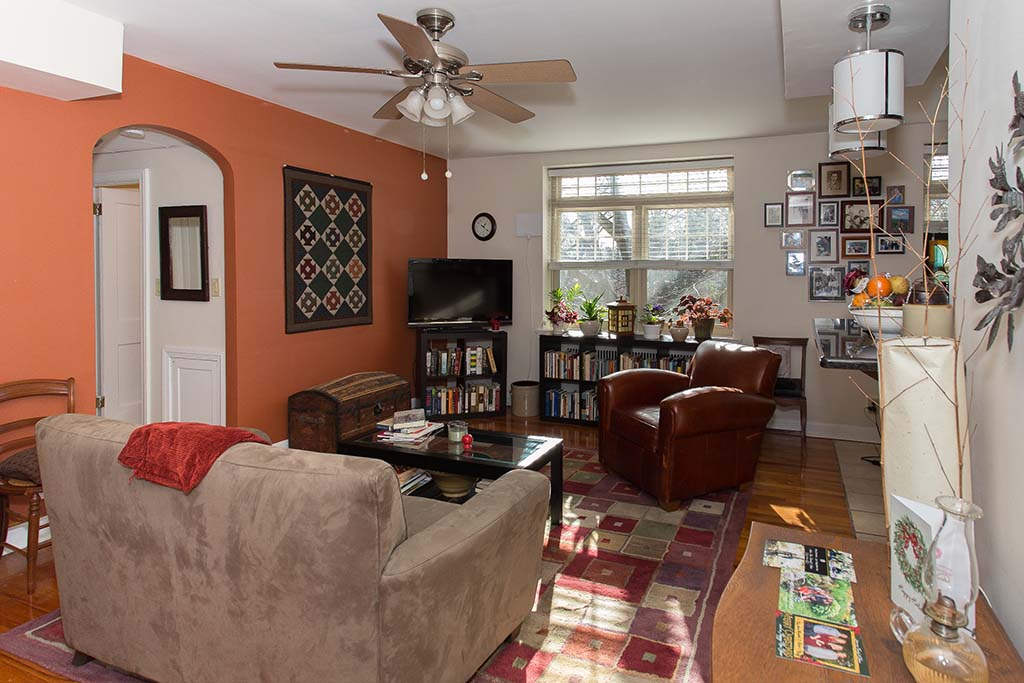 Decorated living room with couch, chair, and TV at Sedgwick Gardens apartments for rent in Philadelphia, PA