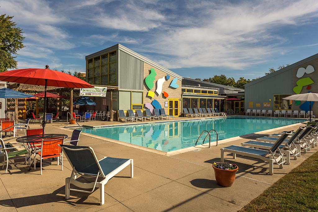 An outdoor pool with lounge chairs and umbrellas at Enclaves at Packer Park apartments for rent