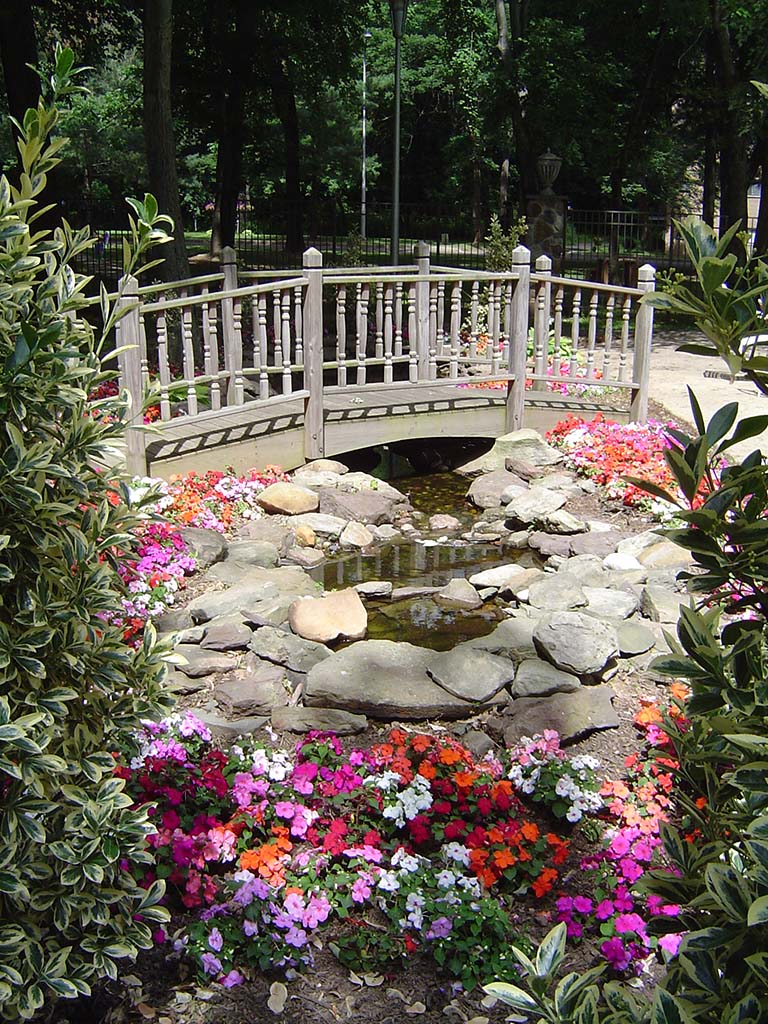 Community garden with a small bridge overlooking flowers and a pond at The Park at Westminster apartments for rent