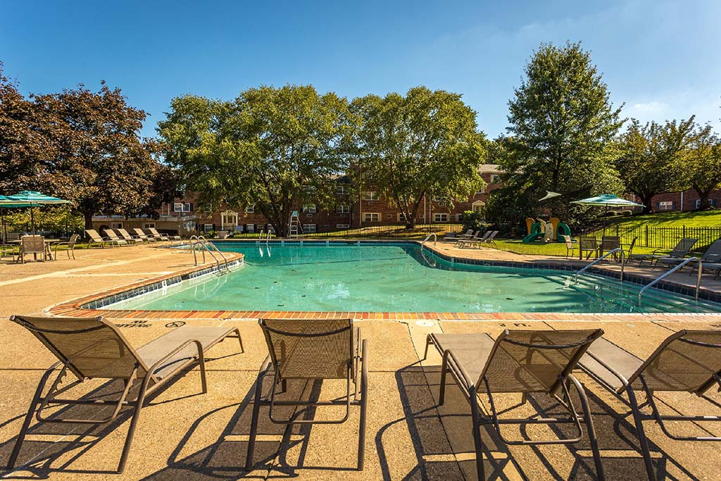 Outdoor pool with lounge chairs and umbrellas at Warrington Crossings apartments for rent