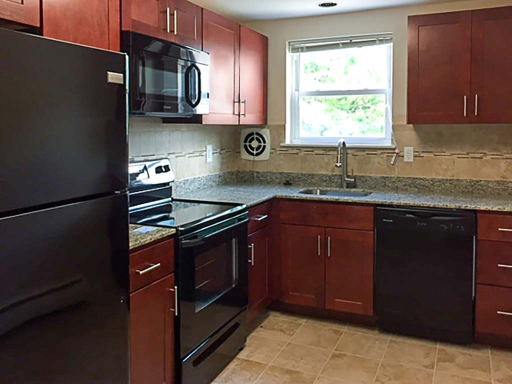 Kitchen with brown cabinetry and energy efficient appliances at Westgate Arms apartments in Jeffersonville, PA