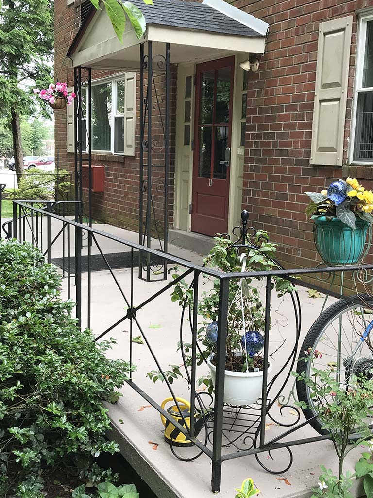 Entrance to a residential building with a porch and flowers at Westgate Arms apartments for rent