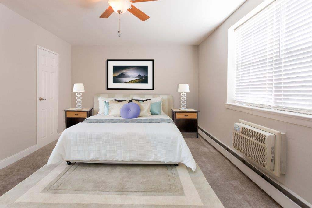 Fully furnished bedroom with a ceiling fan and open window at Willow Bend apartments for rent