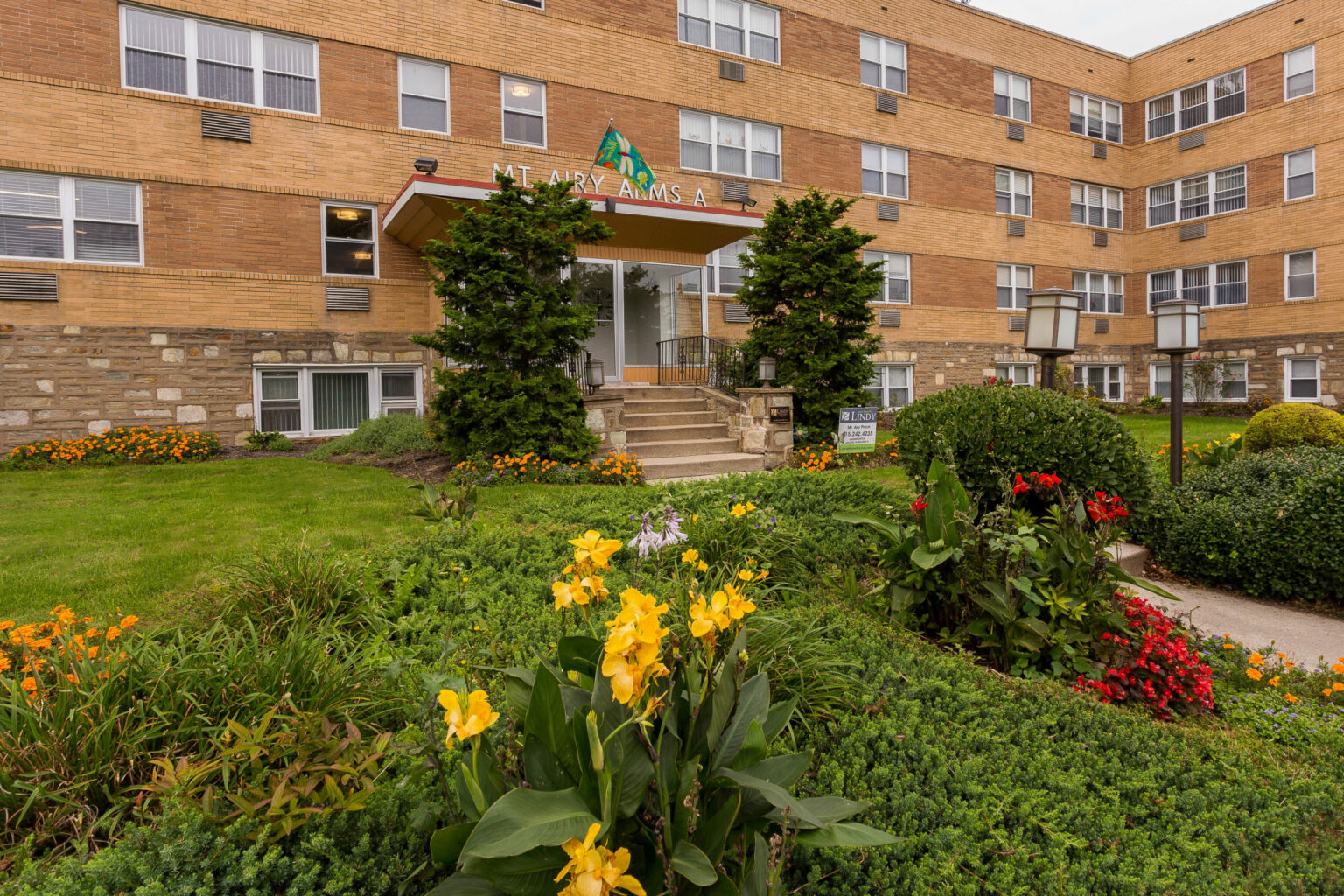 Entrance to Mt Airy Place apartments for rent surrounded by beautifully landscaped grounds with flowers
