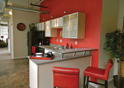 Kitchen with red walls and chairs at St Clair Lofts apartments for rent in Dayton, OH