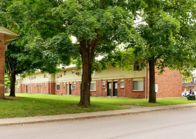 Exterior view of residential apartment buildings for rent surrounded by large green trees