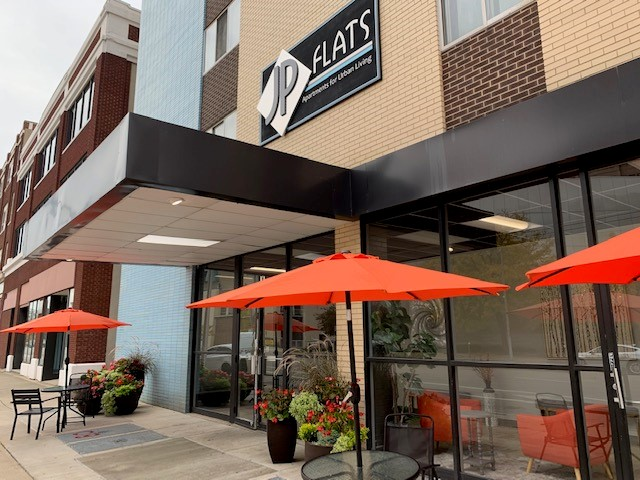 Outdoor seating area with tables and red umbrellas at Flats on Jefferson apartments for rent