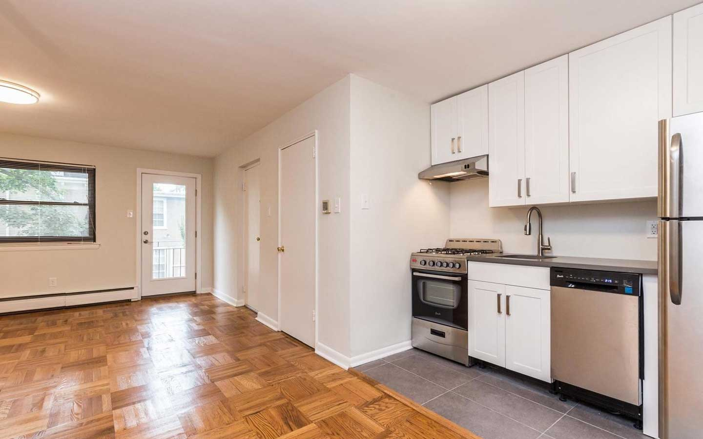 Updated kitchen with sleek tile work with view of open concept living/dining room at Sedgwick Terrace apartments for rent