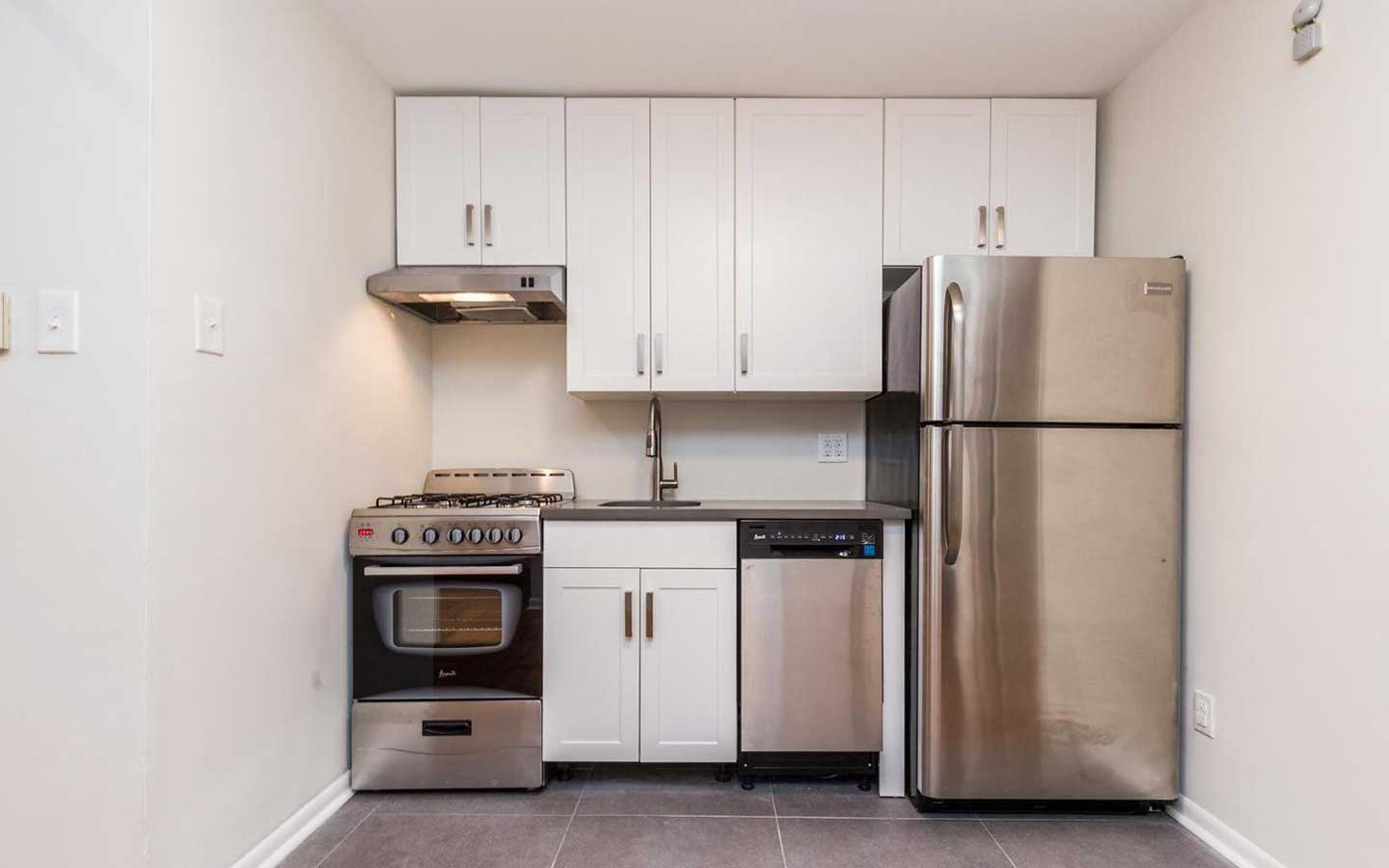 Updated kitchen with stainless steel appliances, sleek tile work, and white shaker cabinetry at Sedgwick Terrace apartments for rent