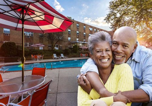 A man and a woman hugging outside at the outdoor pool at Bromley House apartments for rent