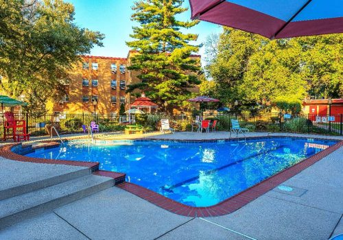 Outdoor pool with lounge chairs and umbrellas at Bromley House apartments for rent
