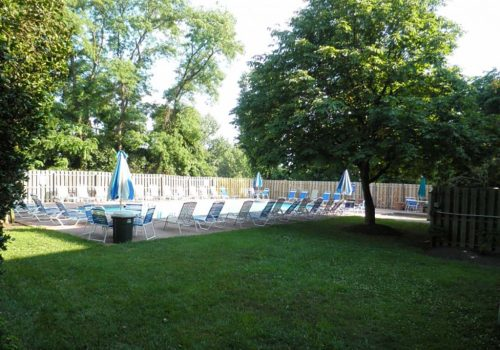 Exterior view of outdoor pool with lounge chairs and umbrellas at Chelbourne Plaza apartments for rent