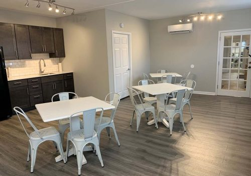 A community kitchen at Crossings at Stanbridge apartments for rent with two tables and chairs