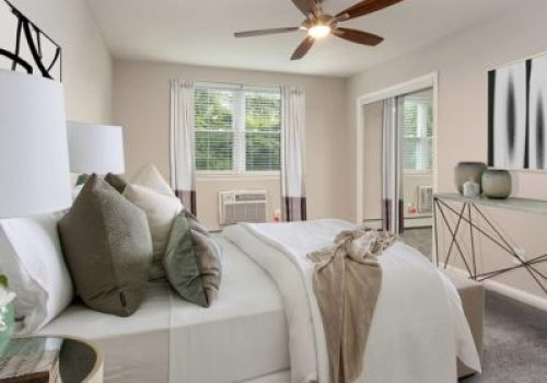 A bedroom with a bed and open windows at Elkins Park Terrace apartments for rent