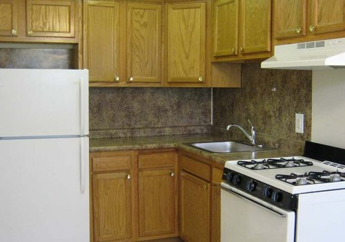 Kitchen with a refrigerator and brown cabinetry at Eola Park apartments for rent in Philadelphia, PA