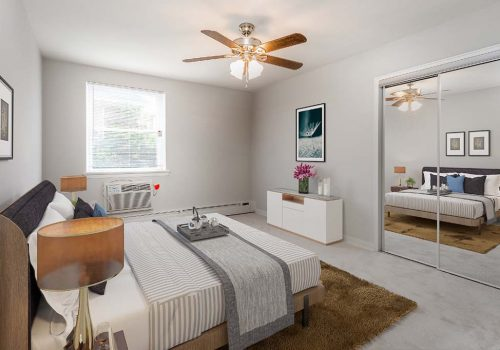 Fully furnished bedroom with a ceiling fan at Eola Park apartments for rent in Philadelphia, PA