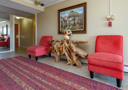 Lobby with two red chairs and a painting at Longwood Manor apartments for rent in Philadelphia, PA