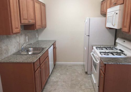 Kitchen with white appliances and brown cabinetry at Longwood Manor apartments for rent