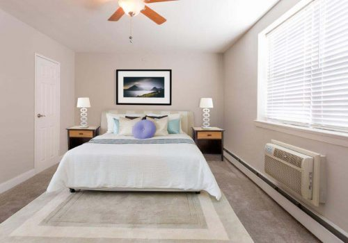 Fully furnished bedroom with a ceiling fan and open window at Mt Airy Place apartments for rent in Philadelphia, PA