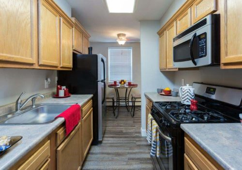Kitchen with black appliances and a dining area at Mt Airy Place apartments for rent in Philadelphia, PA