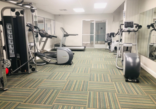 A fully equipped gym at Academia Suites with exercise equipment and weights