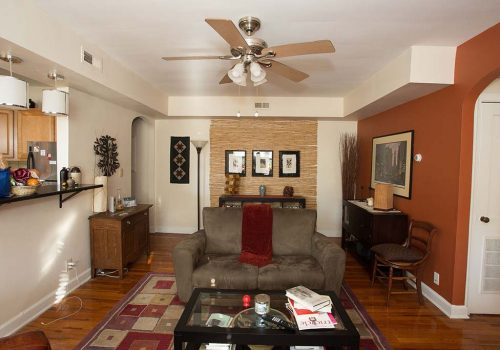 Living room with a couch, table, and chair with a view of the kitchen at Sedgwick Gardens apartments for rent