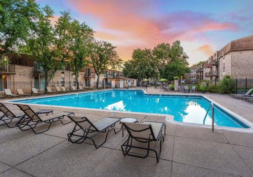 Outdoor pool with lounge chairs and umbrellas at Westgate Arms apartments for rent in Jeffersonville, PA