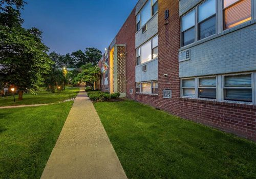 Walkway to residential brick buildings at Willow Bend apartments for rent in Philadelphia, PA