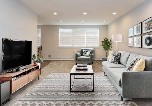 Large living room with a couch, chair, and TV at Willow Bend apartments for rent in Philadelphia, PA