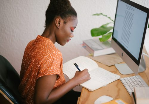 A woman working on a computer and writing in a notebook at Fountain Gardens apartments for rent