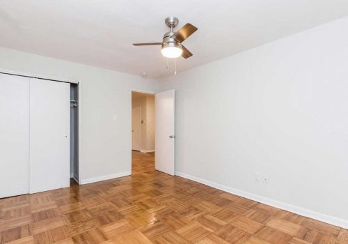 Bedroom with ample closet space, hardwood floors, and ceiling fan at Sedgwick Terrace apartments for rent